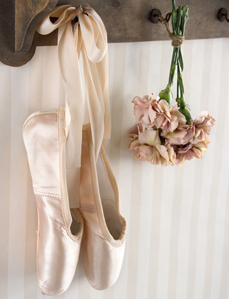 Pair of ballet pointe shoes hanging from a rack